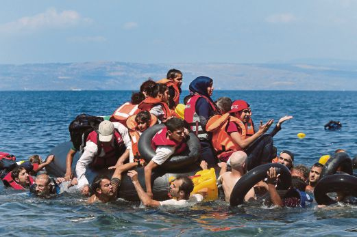 Syrian and Afghan refugees are seen on and around a dinghy that deflated some 100m away before reaching the Greek island of Lesbos, September 13, 2015. Of the record total of 432,761 refugees and migrants making the perilous journey across the Mediterranean to Europe so far this year, an estimated 309,000 people had arrived by sea in Greece, the International Organization for Migration (IMO) said on Friday. About half of those crossing the Mediterranean are Syrians fleeing civil war, according to the United Nations refugee agency. REUTERS/Alkis Konstantinidis