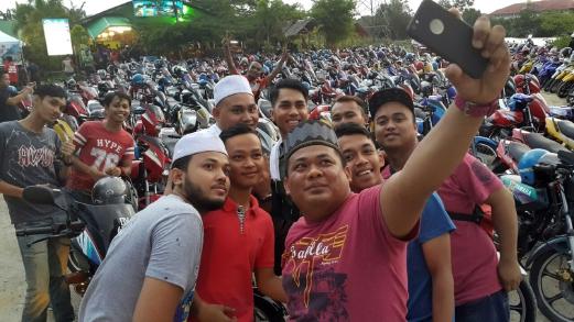 Md Taufik Md Daud,30 (tengah) mengambil gambar selfie bersama sebahagian mat motor yang menyertai Majlis Iftar Ramadan Sek Motor 2016 Kelantan di Restoran Pulau Lima, Bachok.